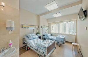 Dwuosobowa sala pacjentów z dużymi łóżkami, umywalką i telewizorem zawieszonym przy suficie