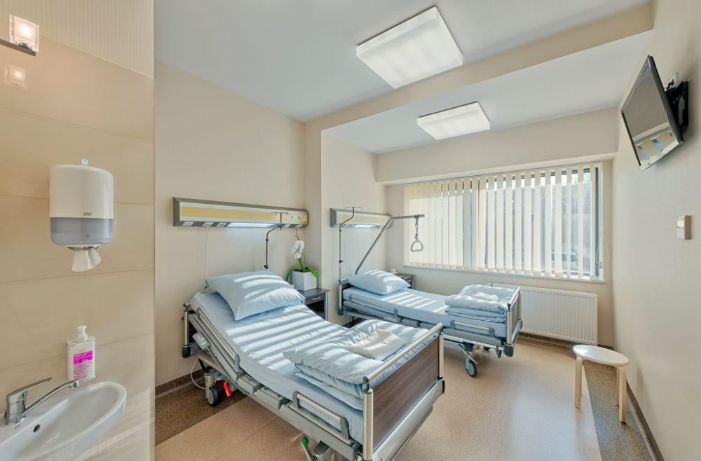 sala pacjentów dwuosobowa z dużymi łóżkami i telewizorem zawieszonym przy suficie