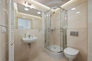 Łazienka z kaloryferem ściennym, prysznicem, umywalką i toaletą w salach dla pacjentów SCM Clinic