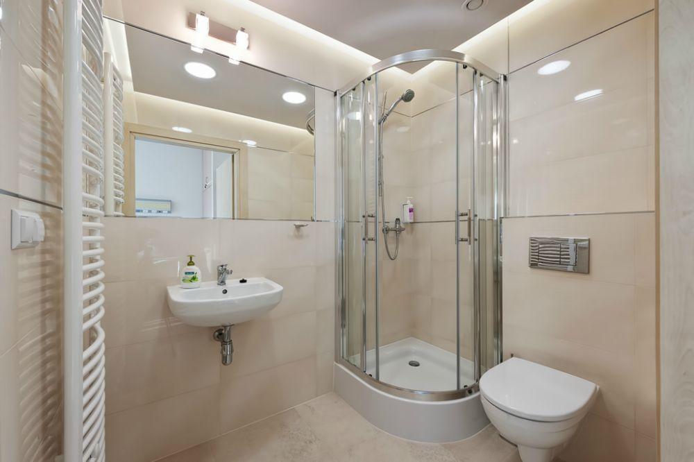 łazienka z kaloryferem ściennym, prysznicem, umywalką i toaletą