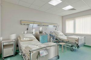 Dwa duże łóżka dla pacjentów w czteroosobowej sali w SCM Clinic w Krakowie