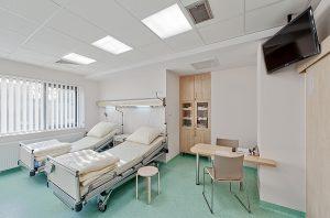 Dwuosobowa sala pacjentów z dużymi łóżkami, stolikiem i telewizorem zawieszonym przy suficie