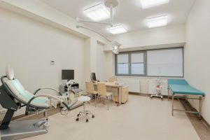 Gabinet lekarski z wygodnym łóżkiem i fotelem medycznym w SCM Clinic