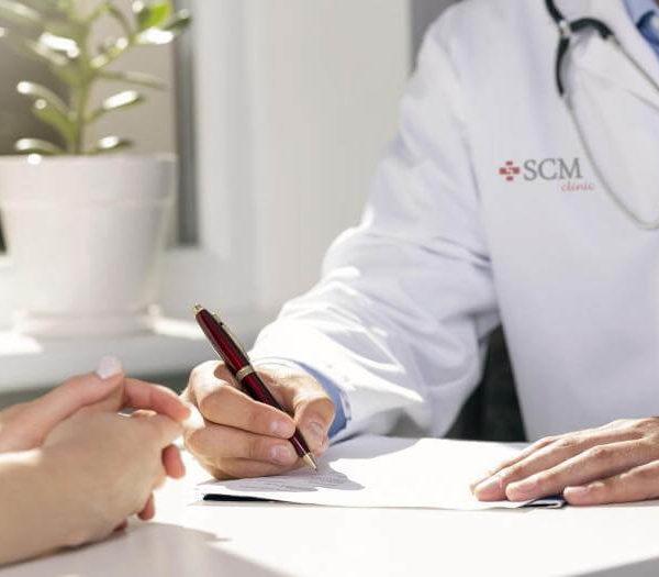 Logo SCM Clinic na fartuchu lekarza udzielającego konsultacji